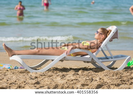 Young tanned woman sunbathing on a sun lounger on the beach against the backdrop of people bathing - stock photo