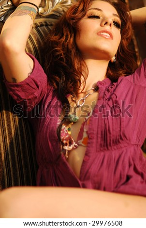 Young tattooed woman in lingerie with long reddish hair - stock photo