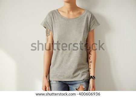 Young tattooed woman wearing grey blank t-shirt. - stock photo