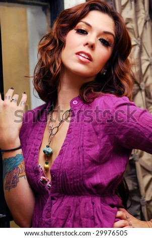 Young tattooed woman wearing purple gauze blouse - stock photo