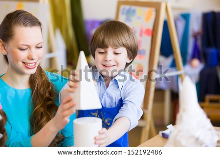 Young teacher and children painting and playing - stock photo