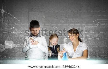 Young teacher and her pupils doing tests at chemistry lesson - stock photo