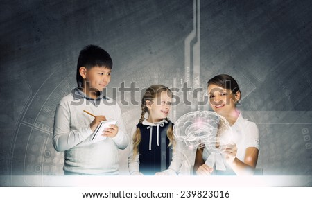 Young teacher and her pupils examining hologram of human brain - stock photo