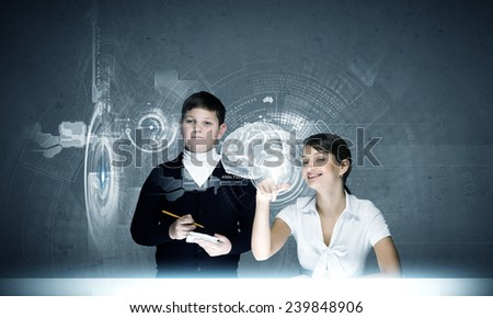 Young teacher and school boy at computing lesson - stock photo