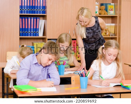 young teacher helps students of primary school in the exam - stock photo