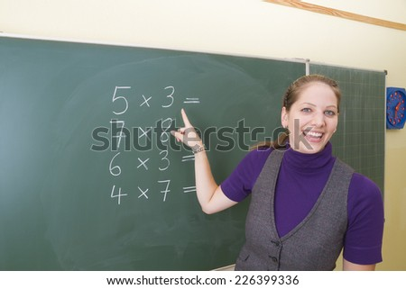 Young teacher in front of a blackboard at school. - stock photo