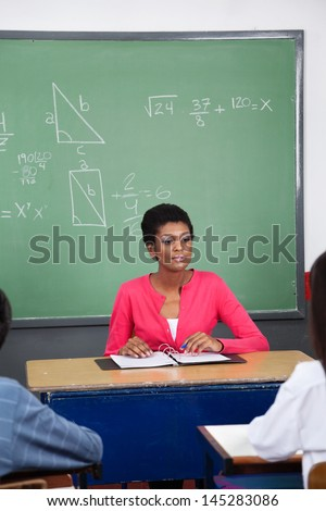 Young teacher sitting at desk with students in foreground at classroom - stock photo