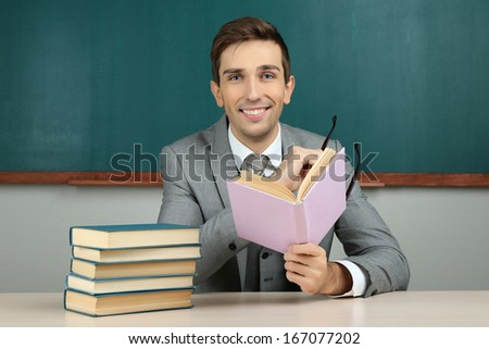 Young teacher sitting in school classroom
