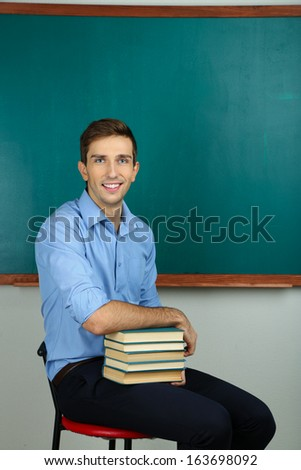 Young teacher sitting near chalkboard in school classroom