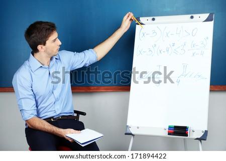 Young teacher sitting near chalkboard in school classroom - stock photo