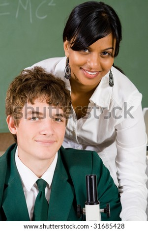 young teacher teaching high school student how to use microscope - stock photo