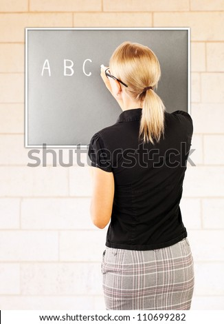 Young teacher write on blackboard, smart woman teaching pupil, rear view of educator explaining homework, beautiful young female professor standing near chalkboard in classroom, education concept - stock photo