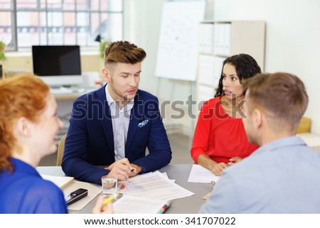 Young Team Leader Businessman Talking to his Three Colleagues at the Office Table during the Meeting. - stock photo