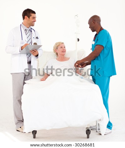 Young team of Doctors at  a patients bedside - stock photo