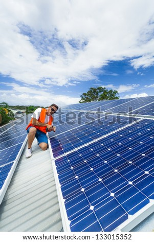 Young technician installing solar panels