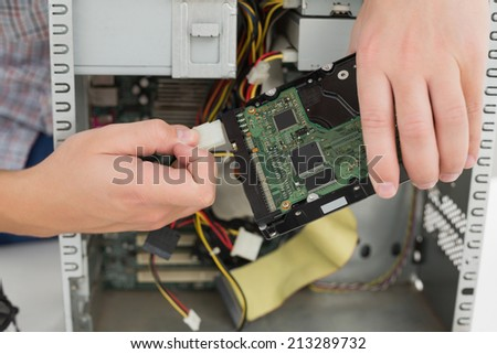 Young technician working on broken computer in his office - stock photo