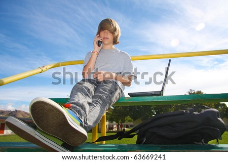 Young teen aged boy talking on cell phone, sitting on bleachers with a laptop beside him. - stock photo