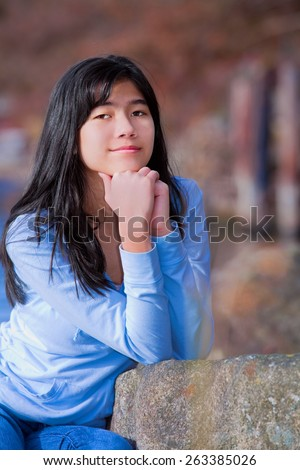 Young teen biracial girl in blue shirt and jeans quietly resting elbows on rock along lake shore, sitting  with serious expression - stock photo