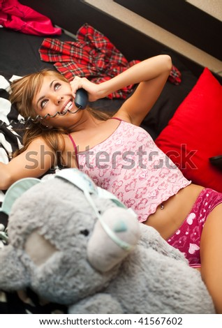 young teen blond woman in bed in chaos of clothes has telephone conversation - stock photo