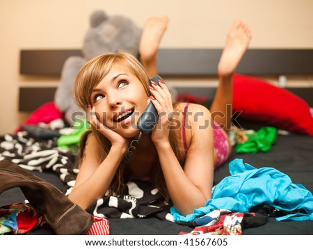 young teen blond woman in bed in chaos of clothes has telephone conversation