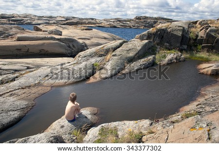 Young teen boy sitting over the sea at the rock. Verdens Ende, World's End, or The End of the Earth is located at the southernmost tip of the island of Tjome in Vestfold, Norway. - stock photo
