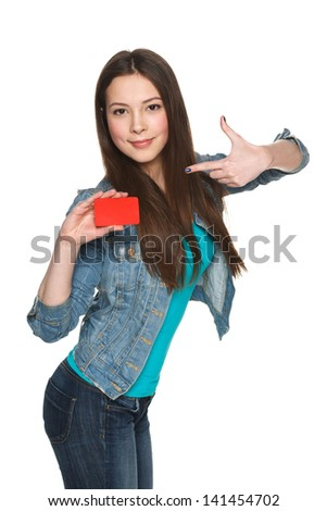 Young teen female holding blank credit card and pointing at it against white background - stock photo