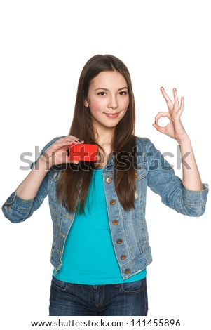 Young teen female showing blank credit card and gesturing OK against white background - stock photo