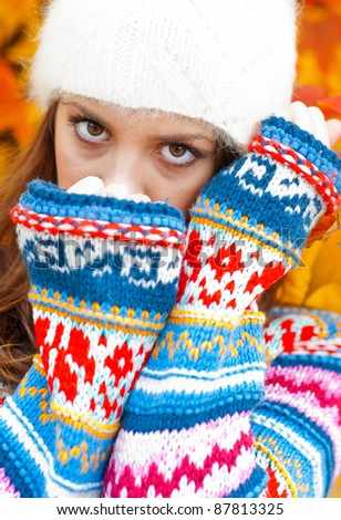 young teen girl hiding her face , wearing colorful sweater in autumn scenery