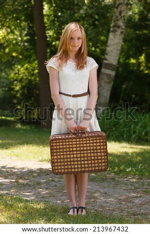 Young teen girl on a path with a suitcase - stock photo
