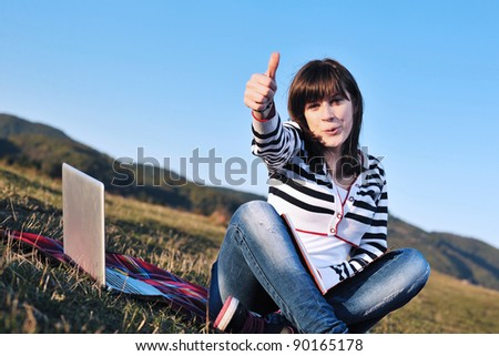 young teen girl read book and study homework outdoor in nature with blue sky in background - stock photo