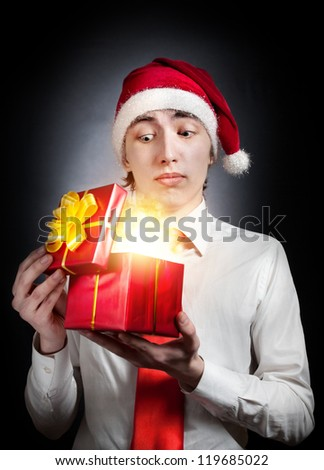 Young teen in Christmas hat opening red gift box with glowing light inside at black background - stock photo