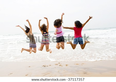 young teen jumping on beach - stock photo