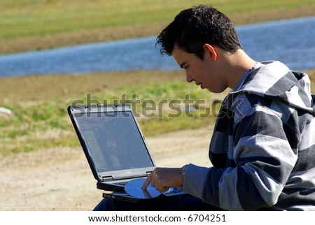 Young teen laptop man at countryside next to water.