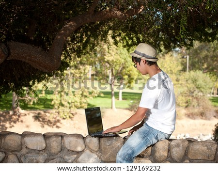 Young teen with hat working on laptop - stock photo