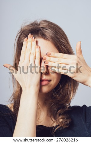 Young teen woman covering her eyes isolated on a gray background - stock photo