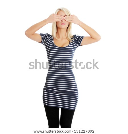 Young teen woman covering her eyes, isolated on white background - stock photo