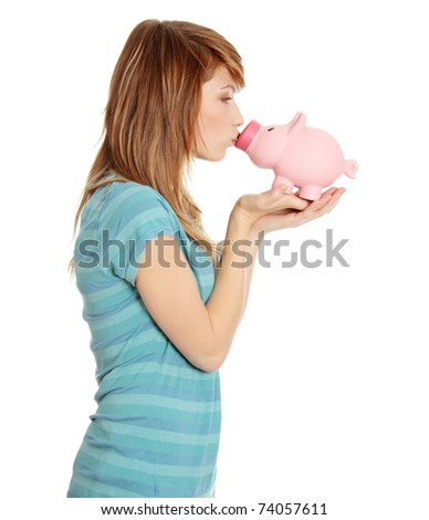 Young teen woman kissing a piggy bank, isolated on white - stock photo