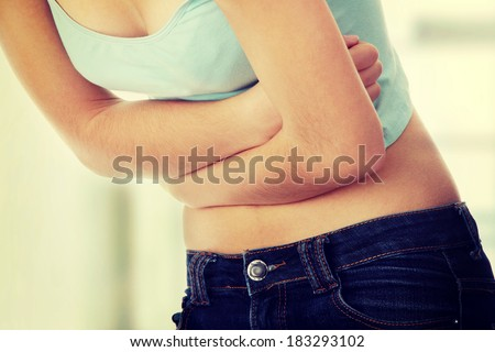 Young teen woman with stomach ache - stock photo