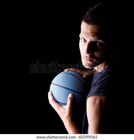 Young teenage basketball player in a studio setting with hip athletic clothing. - stock photo