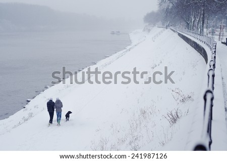Young teenage couple and dog walking beside river on snowy winter day. - stock photo