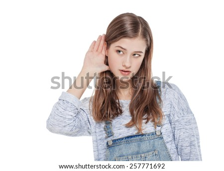 Young teenage fashion girl in jeans overalls holds his hand near his ear and listening  - stock photo