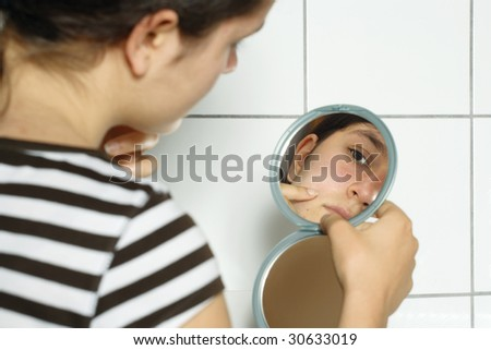 Young teenage female holding a mirror looking at her complexion with concern. - stock photo