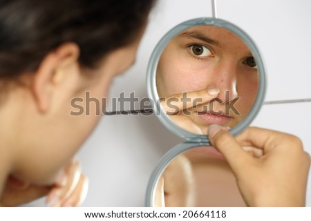 Young teenage female holding a mirror looking at her pimple with concern. - stock photo