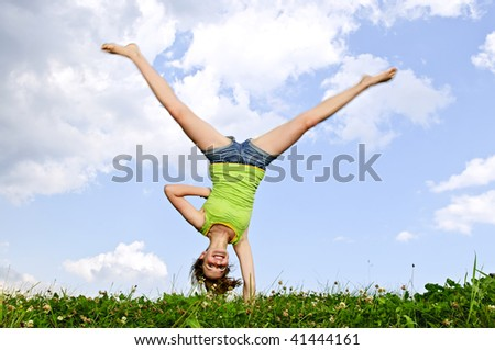 Young teenage girl doing cartwheel in a summer meadow