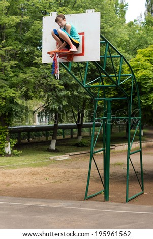 Young teenage girl fixing a basketball net sitting crouched on the hoop on the goalpost as she threads it round the metal hoop