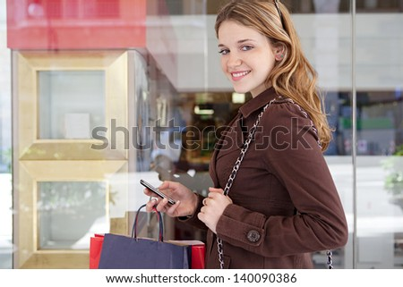 Young teenage girl holding a smartphone and paper shopping bags while in a shopping street with store window glass reflections in the background, turning and smiling at camera. - stock photo