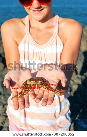 Young teenage girl holding and showing Atlantic crab in her hands. Multicolored outdoors summertime vertical image. Tenerife, Canary Islands, Spain. - stock photo