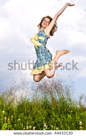 Young teenage girl jumping in summer meadow amid wildflowers - stock photo