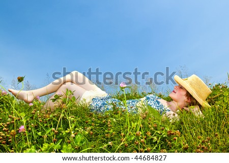 Young teenage girl laying barefoot on summer meadow in straw hat