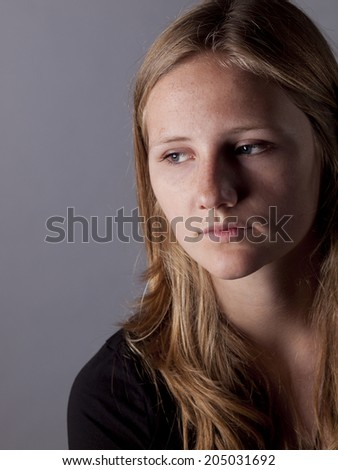Young teenage girl looking sad or depressed over a gray background - stock photo